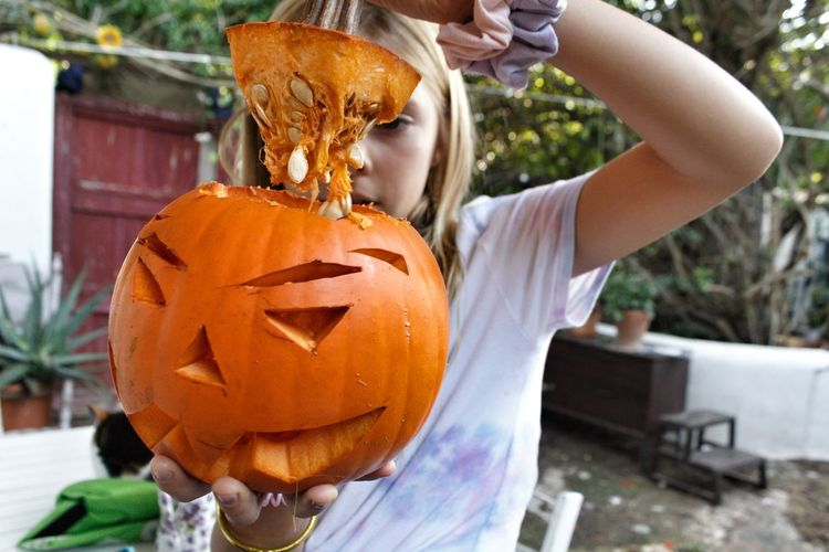 Midsection of woman with pumpkins