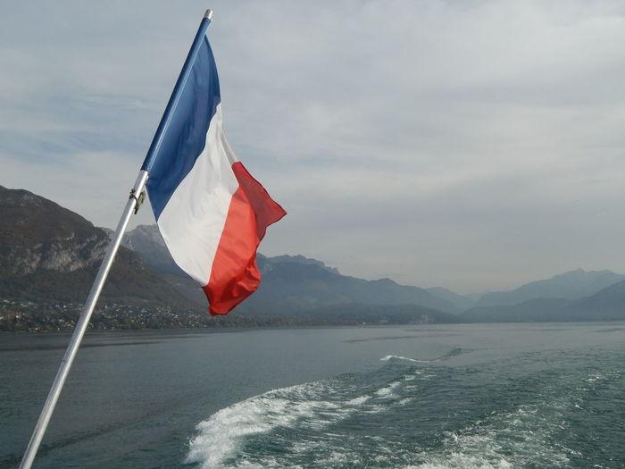 Red flag on sea against mountain range