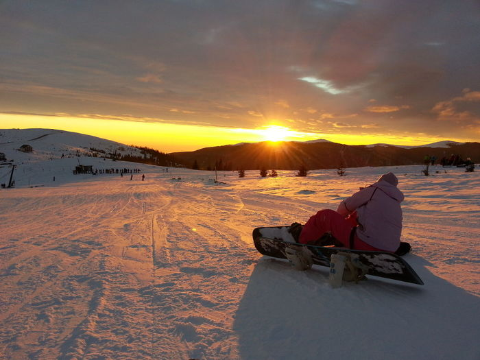 Person Snowboarding On Snow Covered Field During Sunset