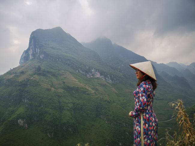 Young Vietnamese women facing and pose for camera with stunning view of the Nho Que river surrounded by mountains from the Ma Pi Leng pass in northern Vietnam Mountain Cloudy Green Color Meo Vac Vietnam Vietnamese Adult Ao Dai Beauty In Nature Cloud - Sky Day Idyllic Landscape Leisure Activity Lifestyles Looking At View Mountain Mountain Range Nature Non-urban Scene One Person Outdoors People Pose Rain Real People Rear View Scenics - Nature Sky Standing Sunrise Traditional Dress Tranquil Scene Tranquility Valley Women