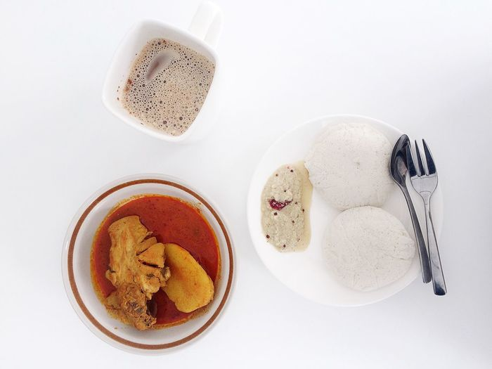 Directly above shot of idli with curry and coffee against white background