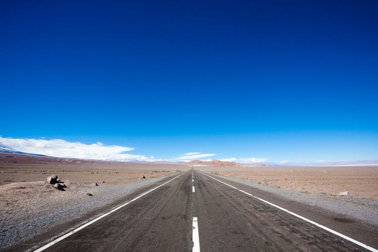 Road amidst desert against blue sky