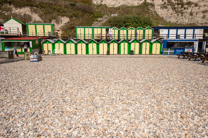 A row of freshly painted traditional wooden beach huts at the bottom of white chalk cliffs in front of the pebble beach of Beer, Devon, UK. Beer, Dorset Dorset Coast Architecture Beach Beach Hut Boundary Building Building Exterior Built Structure Day House In A Row Land Mountain Multi Colored Nature No People Outdoors Pebble Plant Side By Side Solid Tree