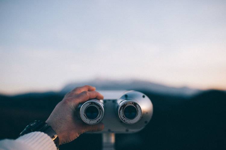 Cropped hand of man holding coin-operated binoculars against sky