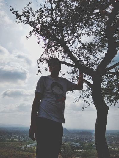 Man standing by tree against sky