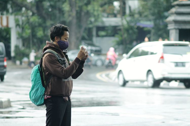 A man with a mask taking a photo against a traffic background