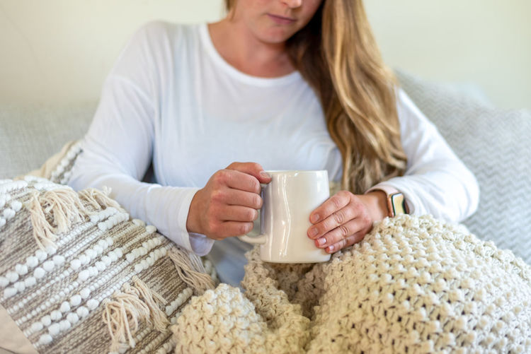Midsection of woman holding coffee cup at home