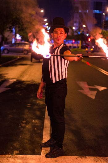 Full length portrait of man performing with fire on street at night