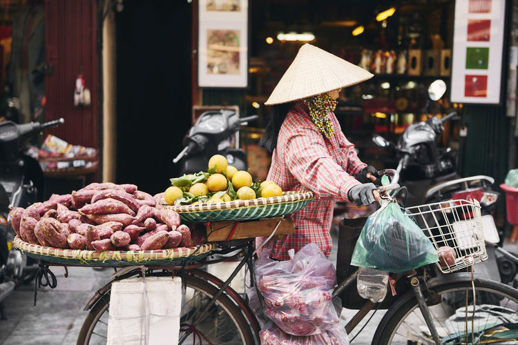 Woman wearing hat selling fruits on bicycle in city