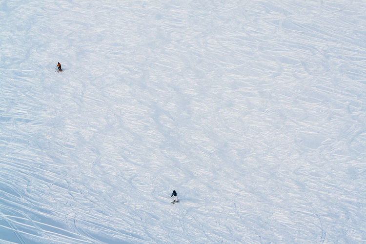 High Angle View Of People Skiing On Snow-Covered Field