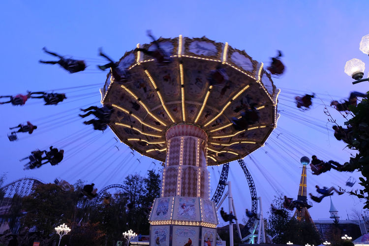 Low angle view of people enjoying in illuminated chain swing ride against sky