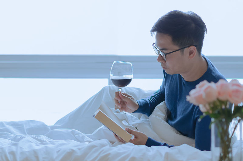 Side view of young man drinking glass on bed