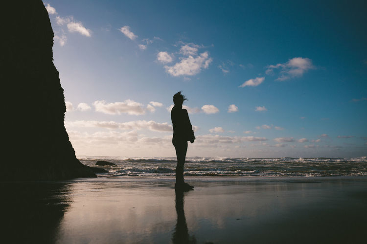 Silhouette woman standing on beach against sky