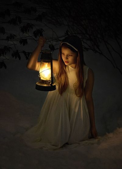 Close-Up Of Girl In Snow With Lamp At Night
