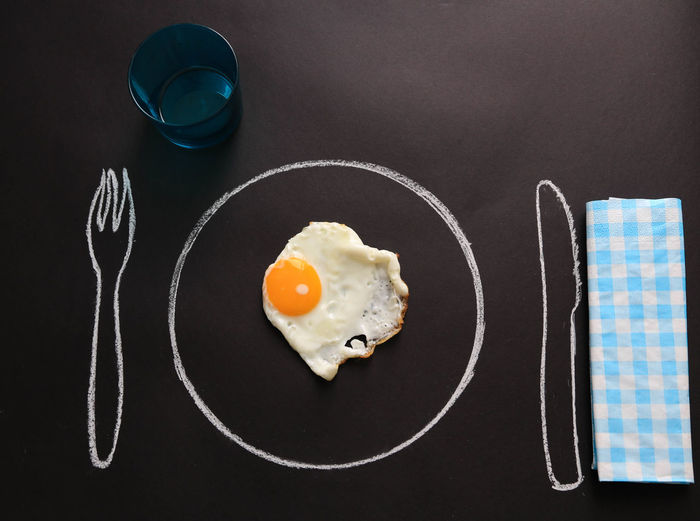 Fried Egg On Drawn Plate At Table