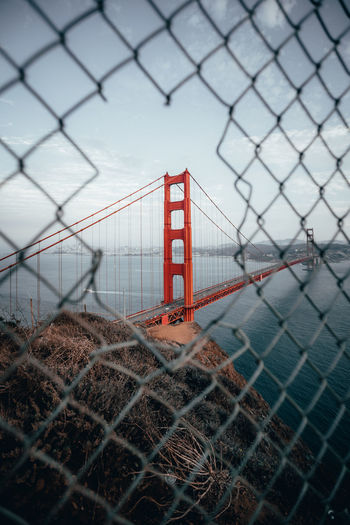 Golden gate bridge over bay against sky seen through damaged chainlink fence