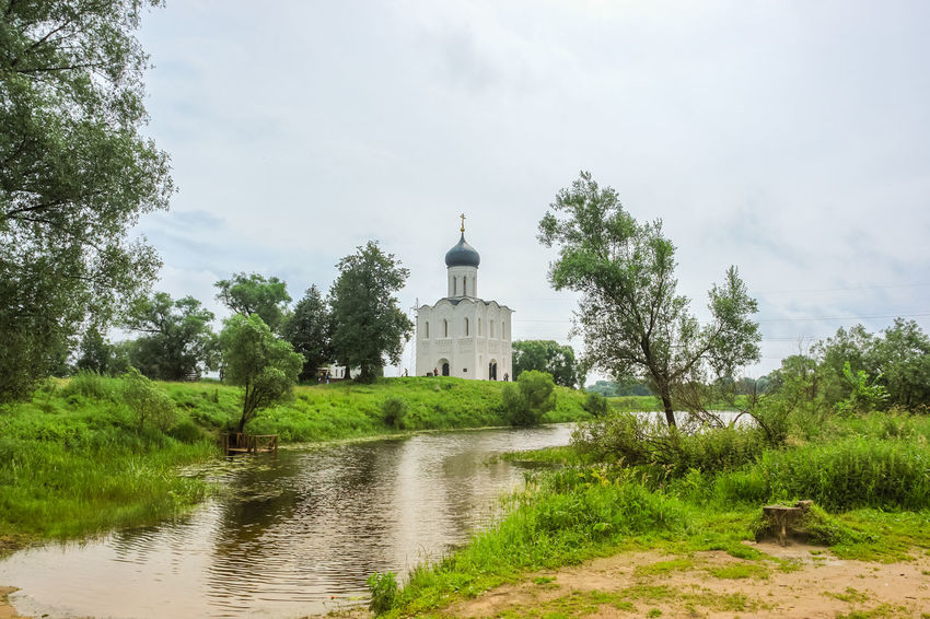 Sunny spring landscape. White church on the river, in the countryside Church Sunnyday☀️ Architecture Country Life Countryside Day Grass Green Color Nature No People Outdoors Plant River Sky Spring Springtime Tree Water