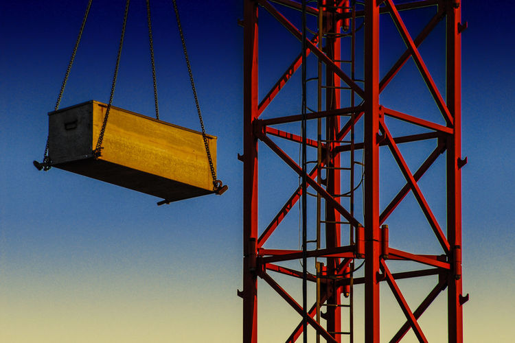 Low angle view of wooden container hanging from crane against blue sky