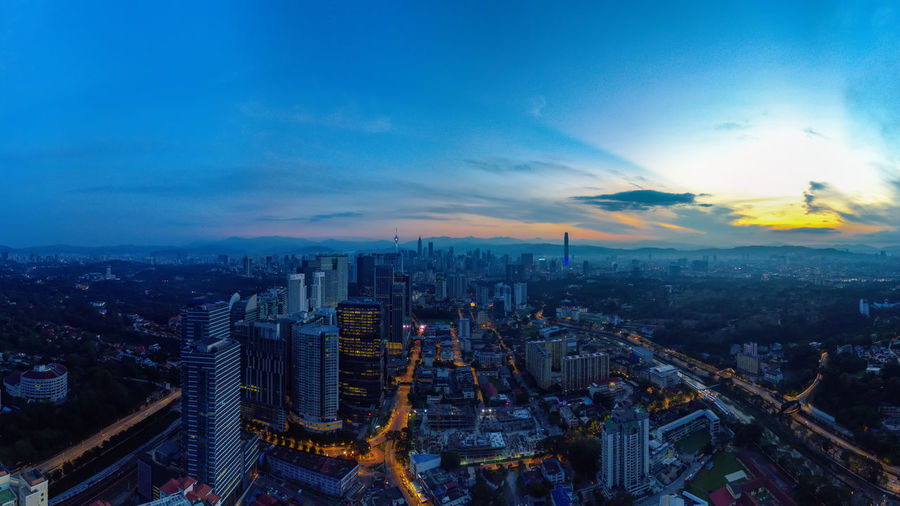 High angle view of illuminated city buildings against sky during sunset