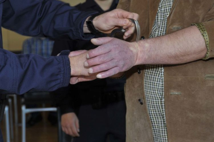 Midsection of police handcuffing man