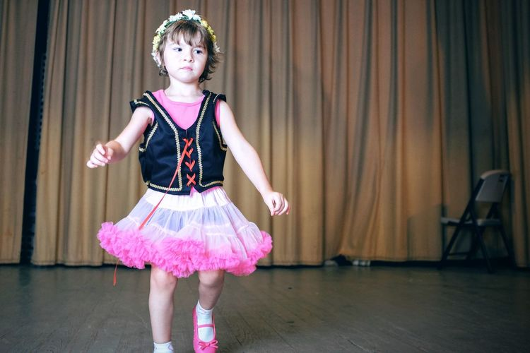 Girl performing against stage curtain