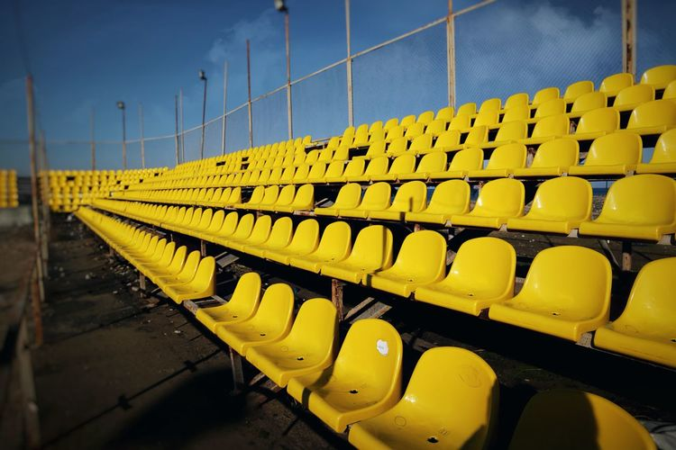 Yellow seats In A Row Yellow Repetition Order Arrangement Sport No People Side By Side Stadium Day Outdoors Seat Absence Security Nature Empty Abundance Chair Bleachers Large Group Of Objects