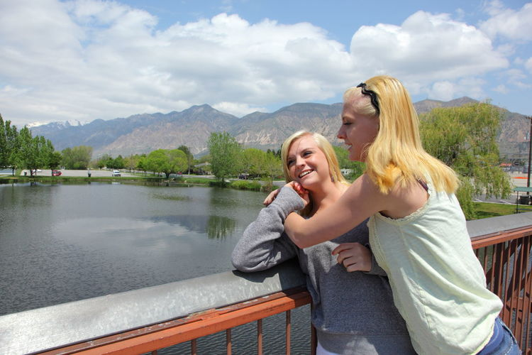 Close-Up Of Girls Embracing Against On Bridge Over River Against Mountains