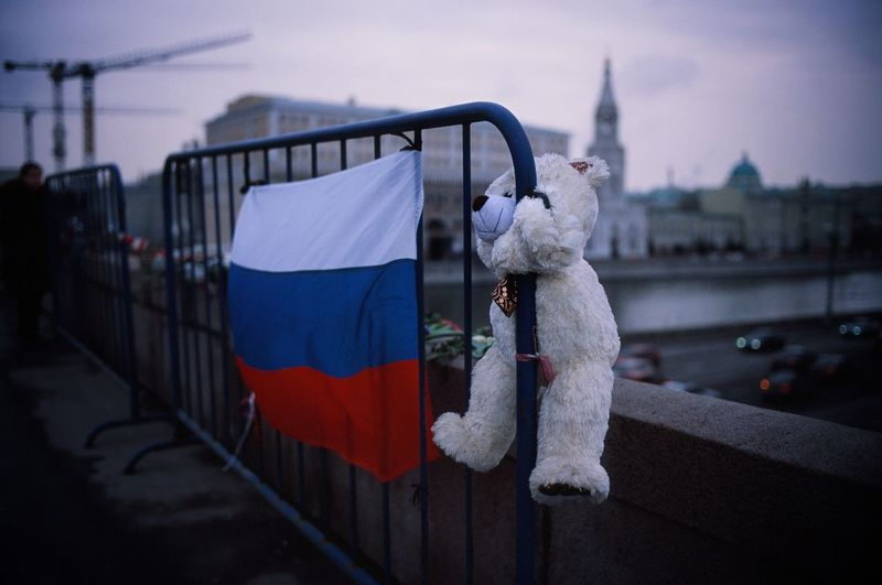 Teddy Bear And Russian Flag On Barricade Against Buildings In City