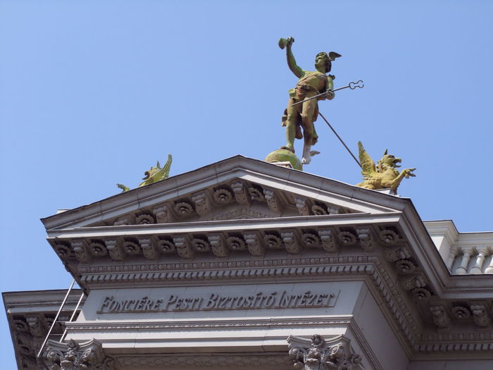Architectural Detail of Bank Building, Andrassy Street Andrássy Street Architectural Detail Architecture Bank Building Blue Sky Bronze Statue Budapest Building Detail Building Exterior Built Structure Capital City Close Up Composition Fun History Human Representation Hungary Low Angle View Male Likeness No People Outdoor Photography Sculpture Statue Travel Destination Unusual