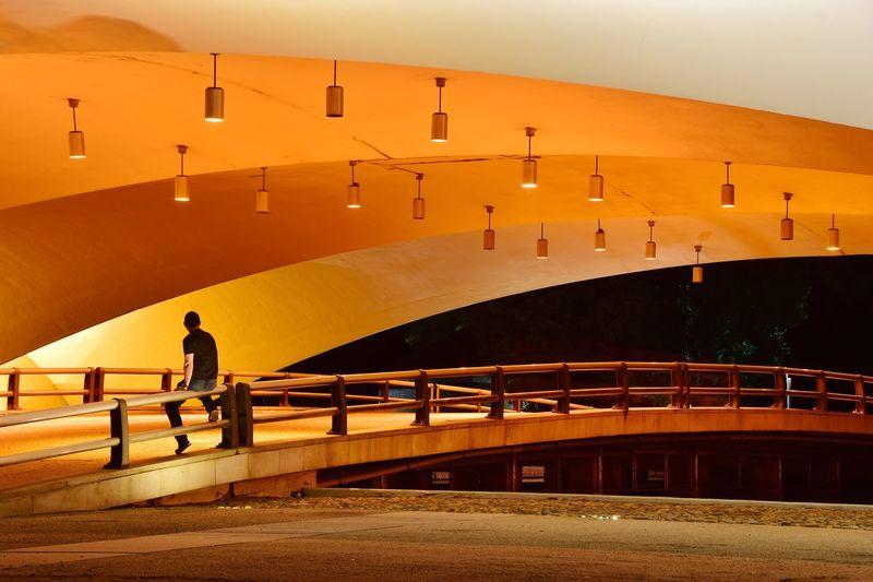 Full length of man sitting on railing below illuminated orange bridge at night