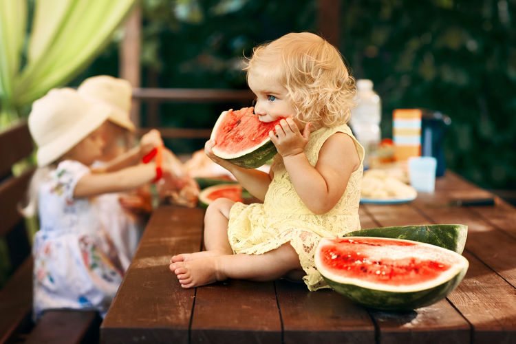 Cute girl eating watermelon while sitting on table