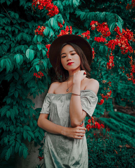 Full length of a beautiful young woman standing against plants