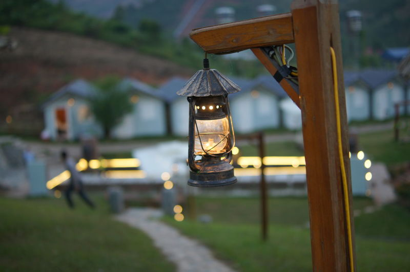 light bulb in twilight Light Twilight Focus On Foreground Hanging Lantern Outdoors