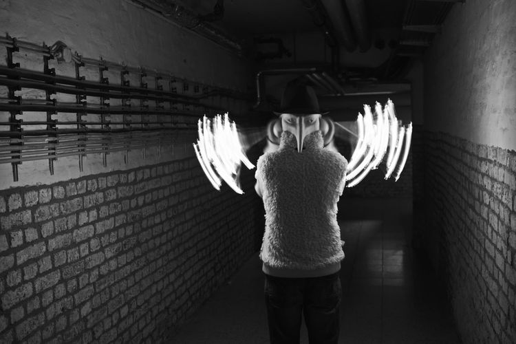 Rear View Of Man Wearing Mask With Light Trails