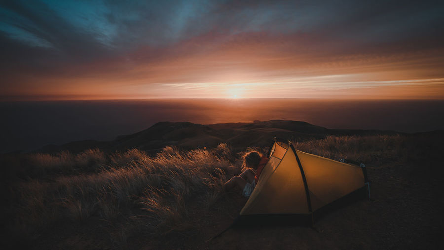 Man sitting in tent during sunset