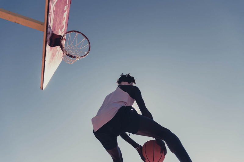 Low angle view of man playing basketball
