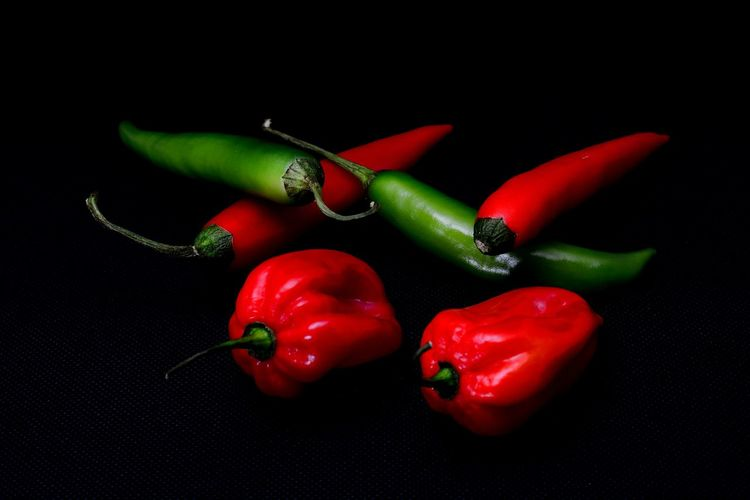 Close-up of red chili peppers on black background