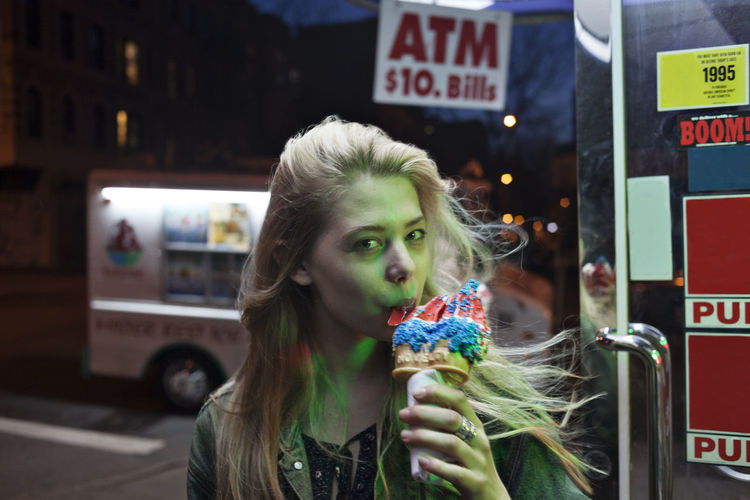Portrait of young woman holding ice cream standing in city