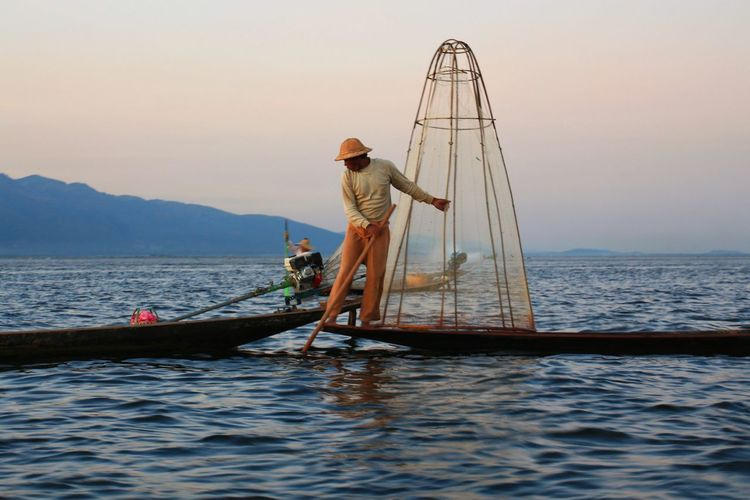 Fisherman showing tricks with net Lake Inle Lake Myanmar Intha Dusk Shan State Evening Working Lifestyle Showing Outdoors Rural Scene Countryside People One Person Real People Real Life A Shot Moment In Time Landscape Journey Amazing Nautical Vessel Water Full Length Men Fisherman Standing Fishing Net Gold Fishing