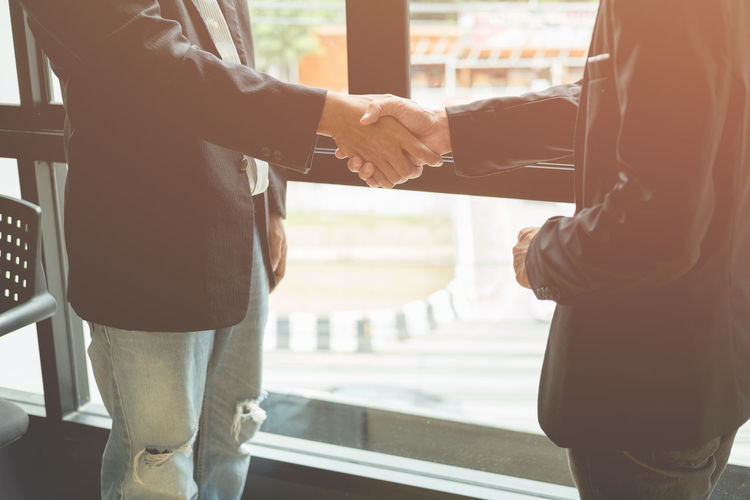 Midsection of businessmen shaking hands while standing by window in office