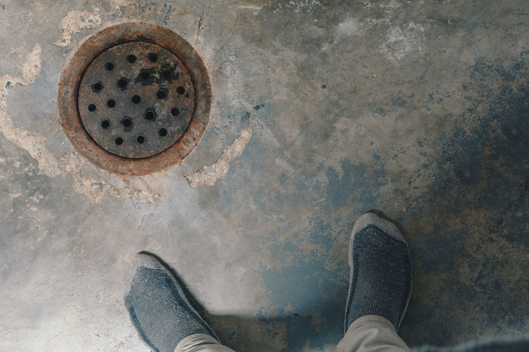 Low section of man standing by sewer in basement