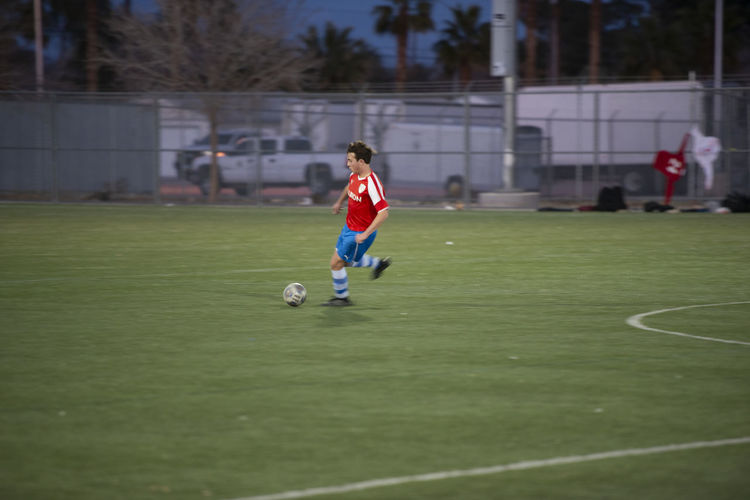 Boy playing soccer ball on field