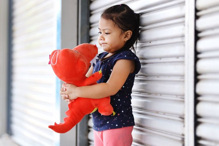 Girl holding stuffed toy while standing by shutter