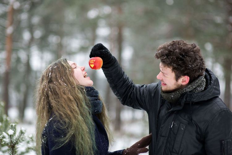Young Couple Eating Apple In Forest During Winter