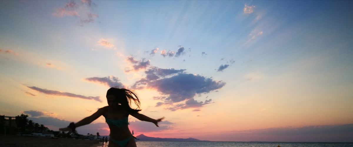 Silhouette woman with arms outstretched standing against sea during sunset