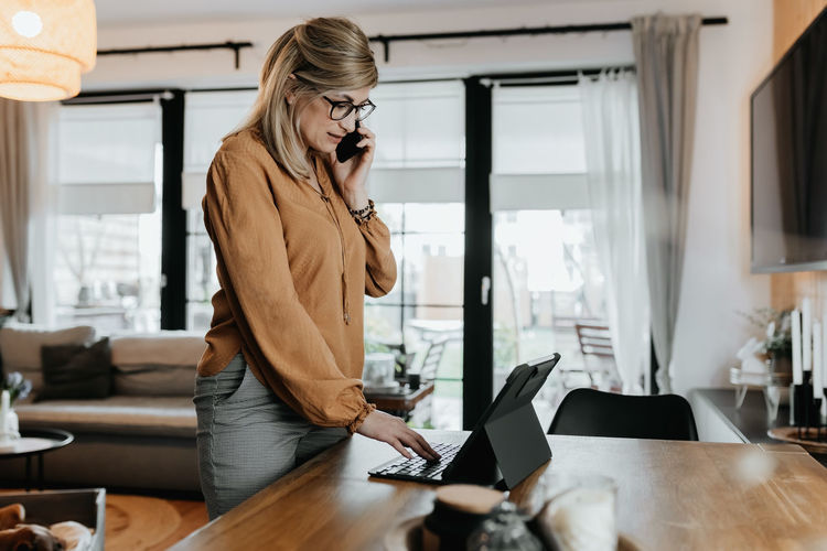Side view of businesswoman talking on phone while using laptop at home