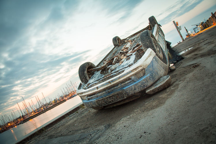 Damaged car at harbor against sky