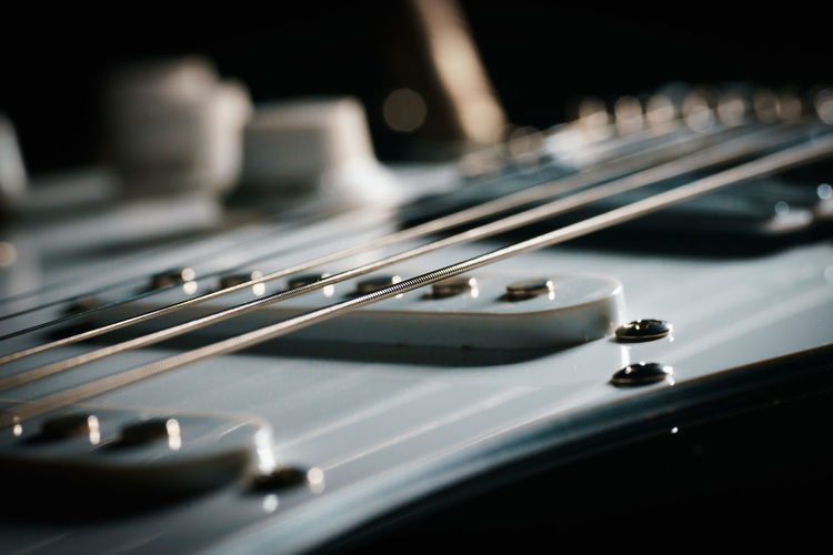 Close up picture of a black electric guitar on a black background.