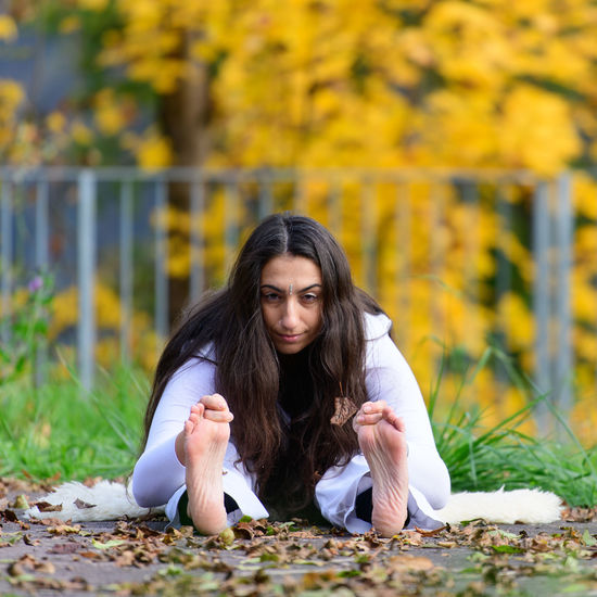 Portrait of woman performing yoga at park