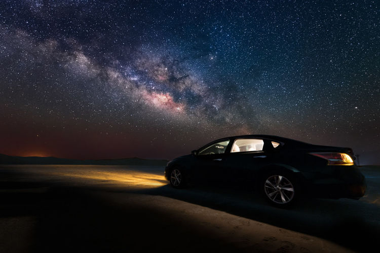Car on illuminated street against sky at night